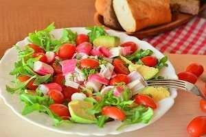 Ensalada con palitos de cangrejo, pimiento verde, tomate, brotes tiernos y aguacate.