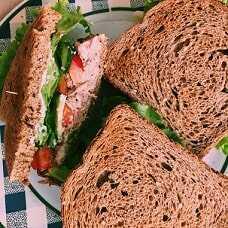 Sándwich integral o de semillas con 1/2 lata de atún, tomate y hojitas